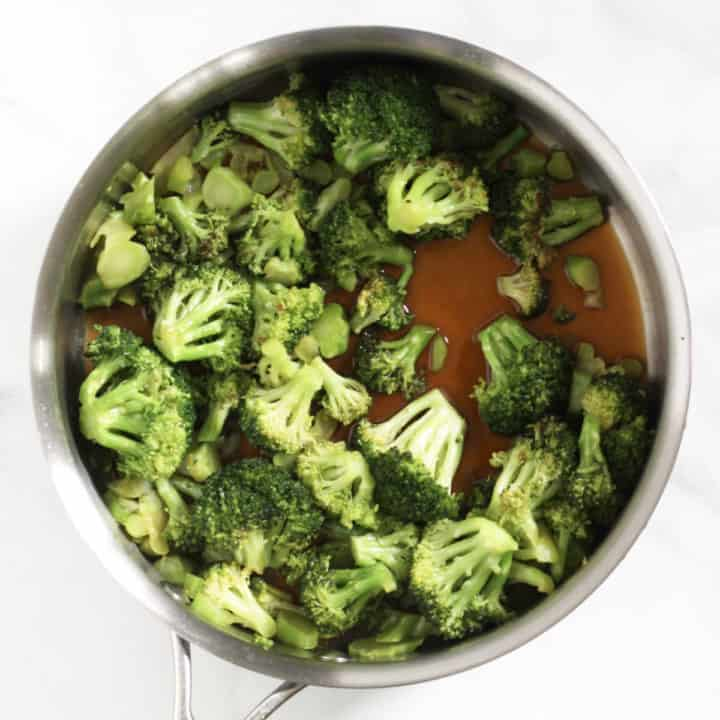 broccoli in pan with added coconut aminos and honey showing on bottom