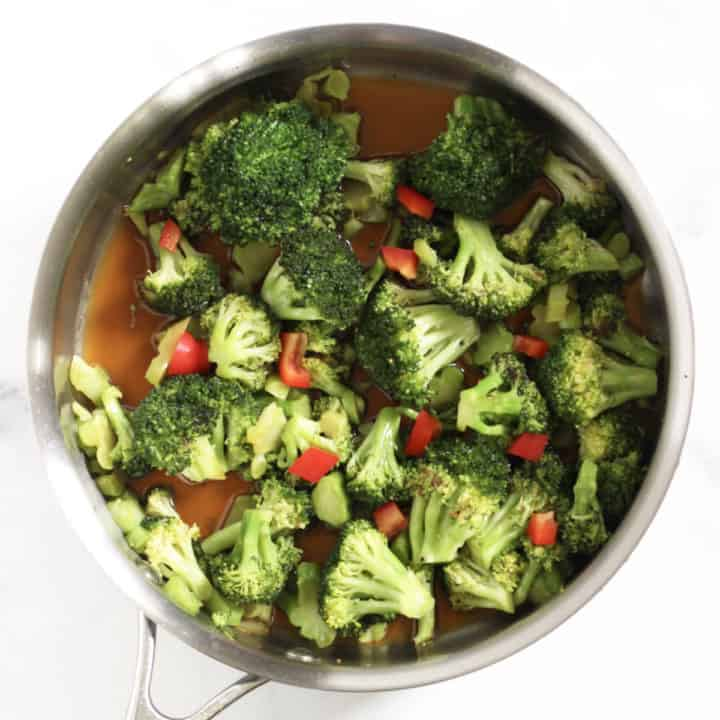 broccoli in pan with sauce and added red pepper