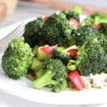 closeup of broccoli stir fry on white plate, viewed from an angle