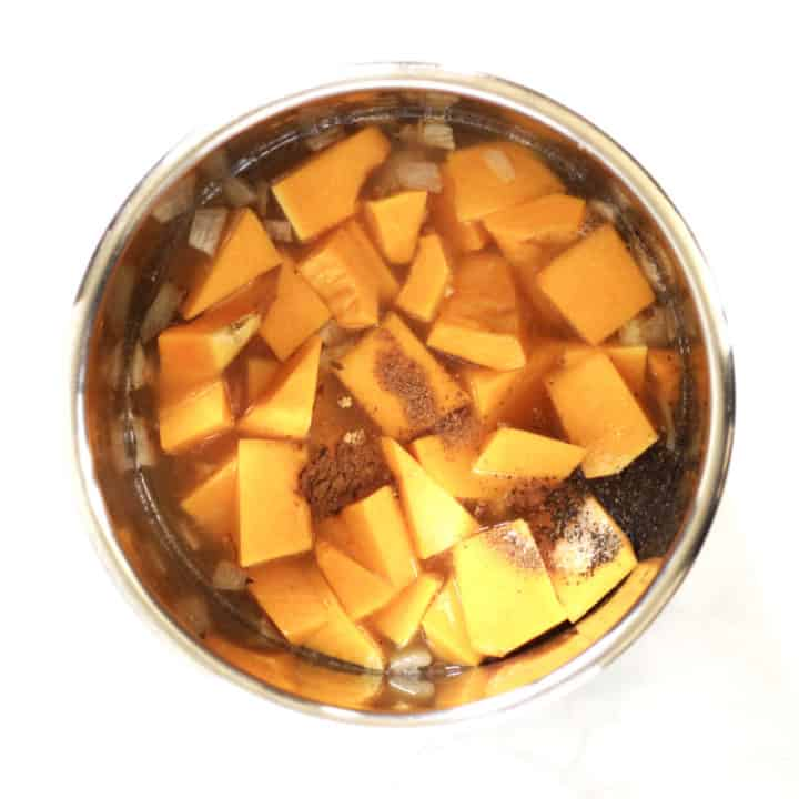 spices sprinkle over chunks of butternut squash in Instant Pot