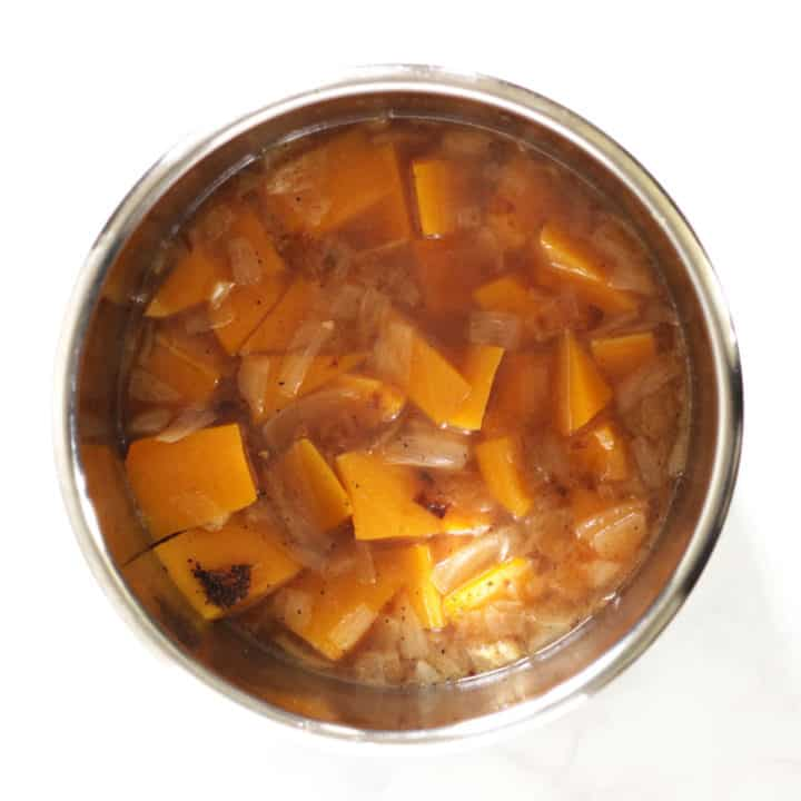 cooked chunks of butternut squash in liquid with spices in Instant Pot