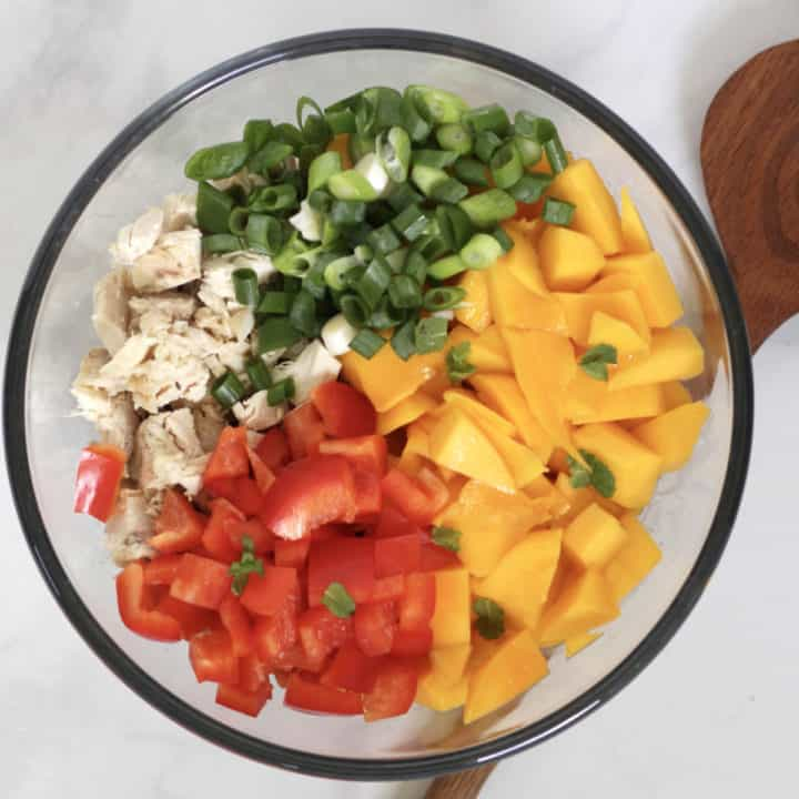looking down on glass bowl of chunks of mango, red pepper, cooked chicken, and green onion