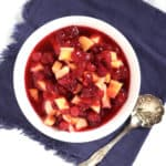 looking down on cranberry sauce with chunks of mango in a white bowl on a lavendar napkin
