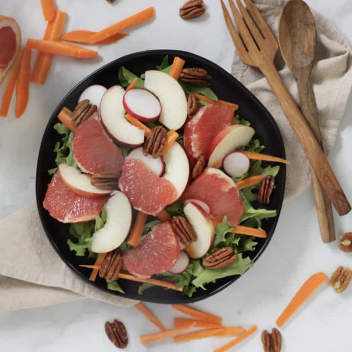 looking down on sliced grapefruit, apples, and radishes, carrots slivers, and pecan halves on a bed of greens