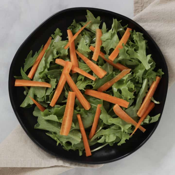 toothpick-shaped slices of carrot arranged on a bed of greens on a black plate