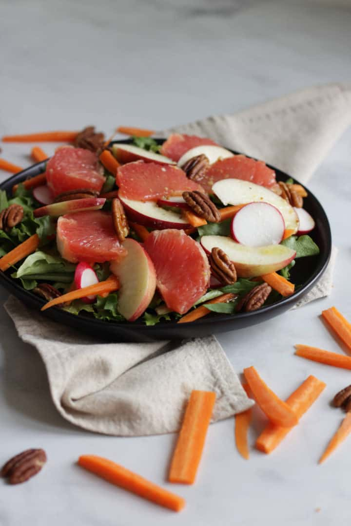 grapefruit salad on black plate seen from a side angle, slim carrot sticks scattered in foreground