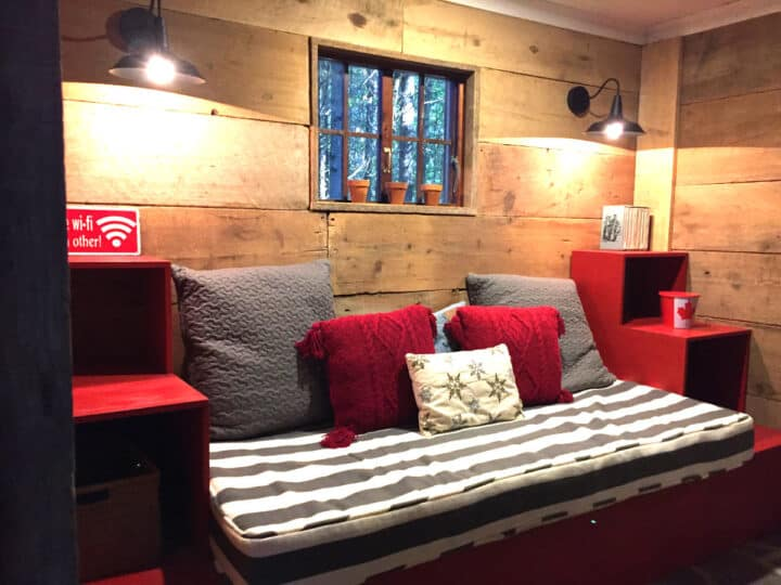 day bed between red shelves in front of wood walls with lights shining down