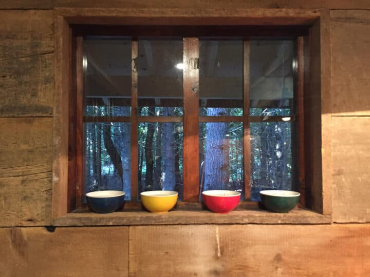 blue, yellow, red, and green bowls sitting on a window sill