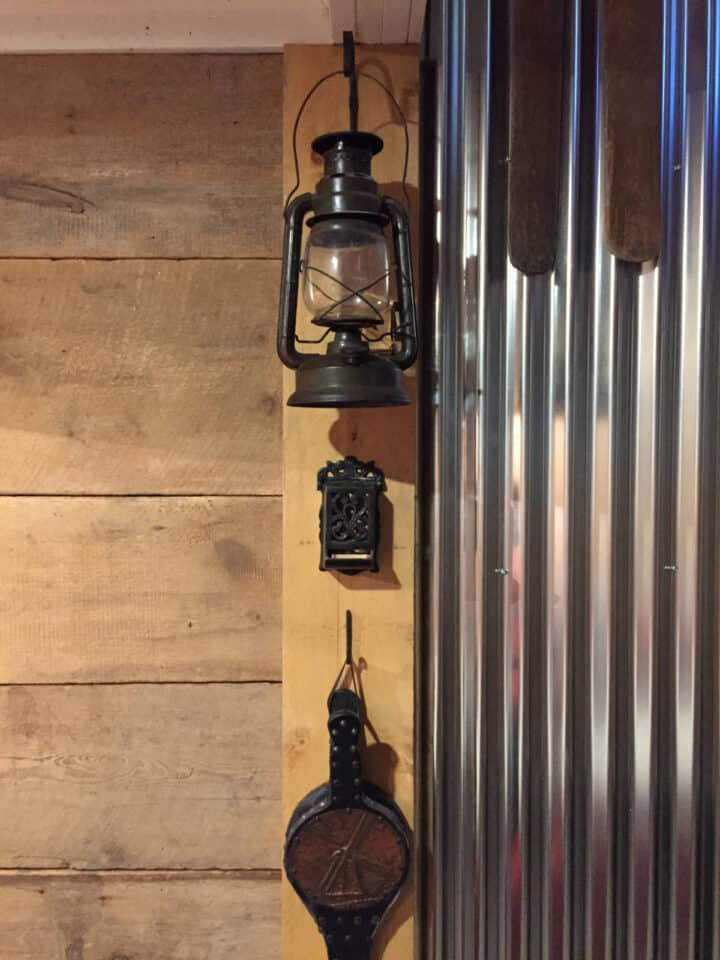 old kole oil lantern and fire accessories hanging on wall