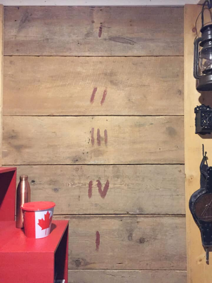 wall of aged wooden boards with various Roman numerals painted on them