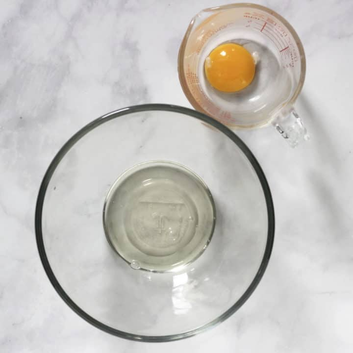 egg yolk in pyrex measuring cup and egg white in glass bowl