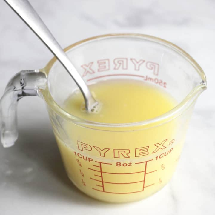 fork stirring pale yellow liquid in measuring cup