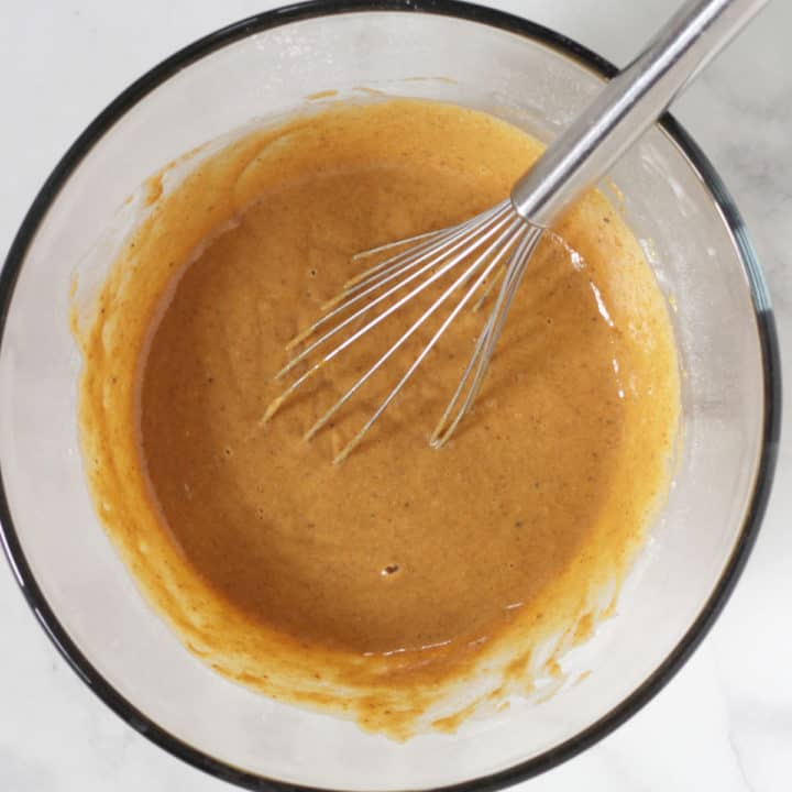 caramel-coloured thick liquid with whisk in glass bowl