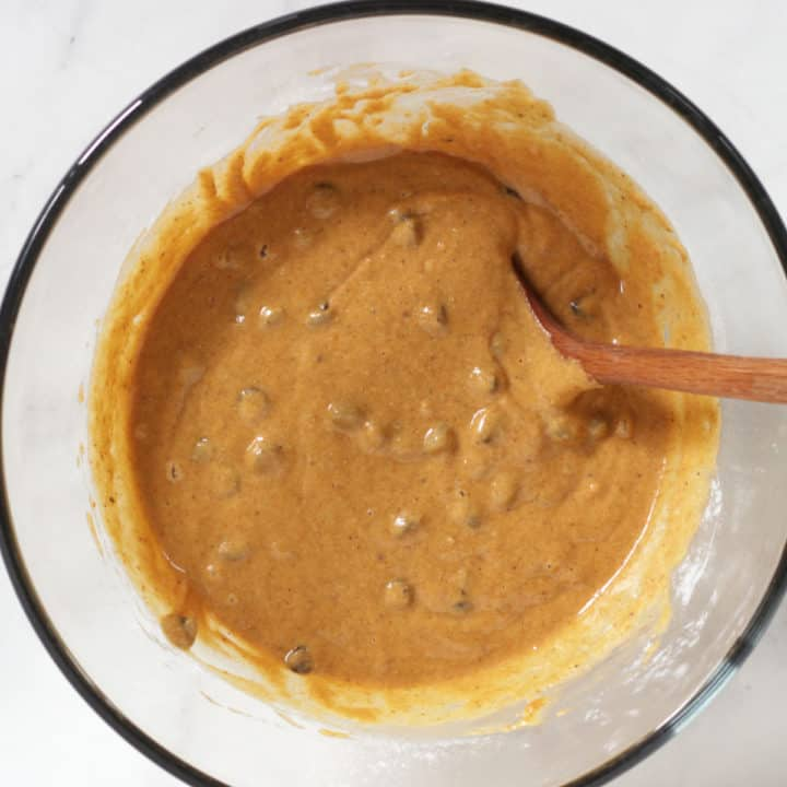 chocolate chips are stirred into golden batter with wooden spoon in clear glass bowl