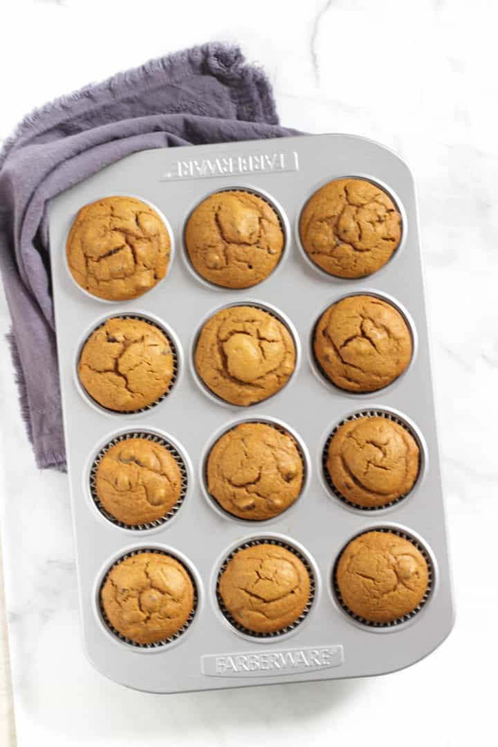 looking down on pan of golden, baked muffins with lavender napkin