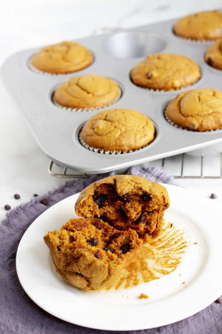 broken open pumpkin muffin with chocolate chips on wrapper on white plate and pan of muffins in background