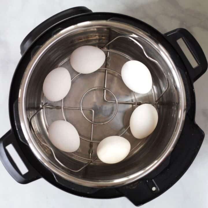 six eggs on trivet with water in Instant Pot