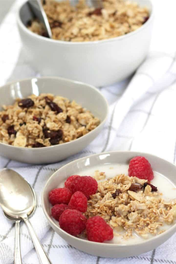 three bowls of homemade granola with berries on the front one