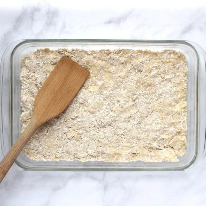 a wooden spatula presses the flour mixture into a glass pan