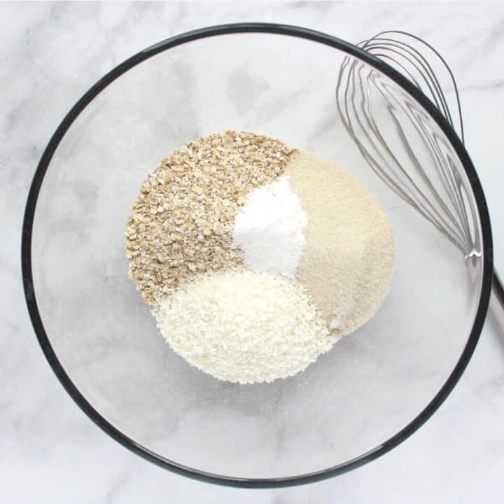 oatmeal, flour, coconut, sugar, baking powder, and salt in glass bowl with whisk to side