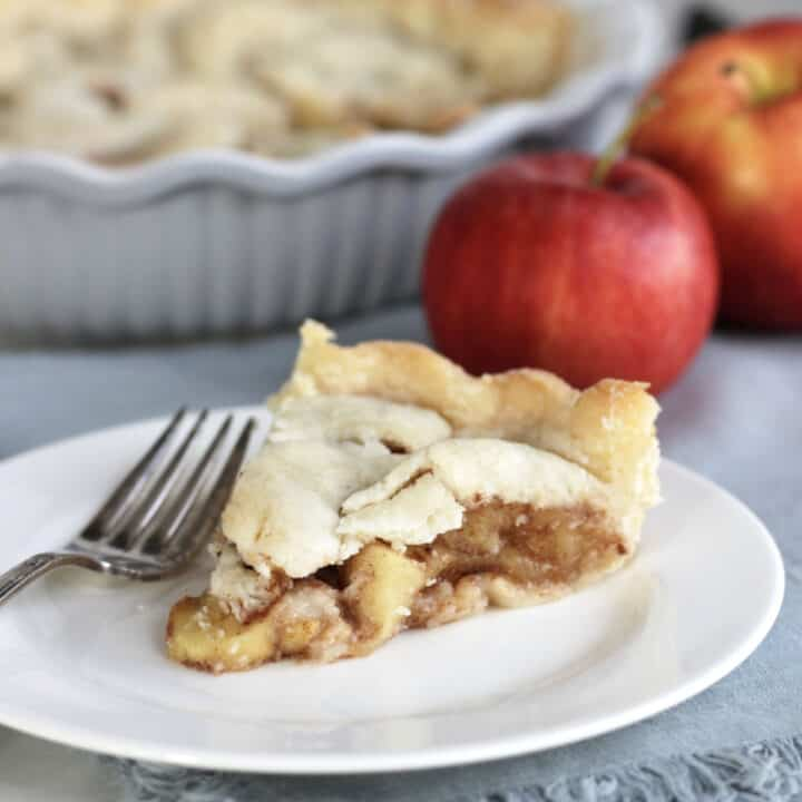 slice of apple pie on white plate with apples and remaining pie in background