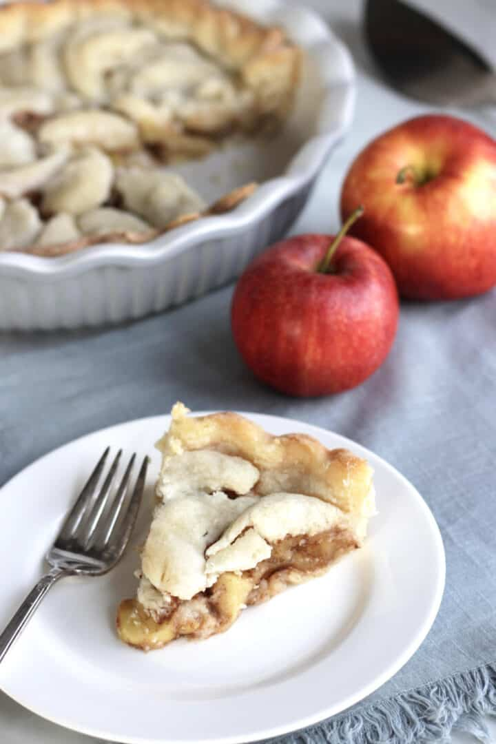 slice of apple served on white plate, with two whole apples and remaining pie in background