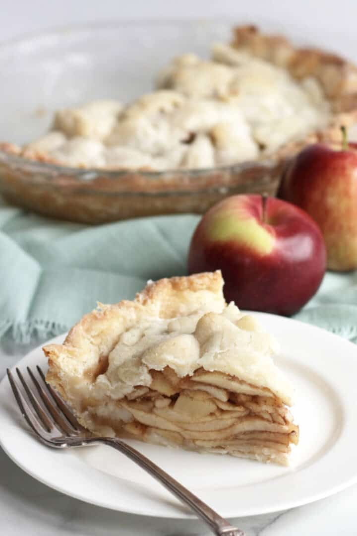 wedge of gluten free apple pie on white plate in front of apples and remaining pie