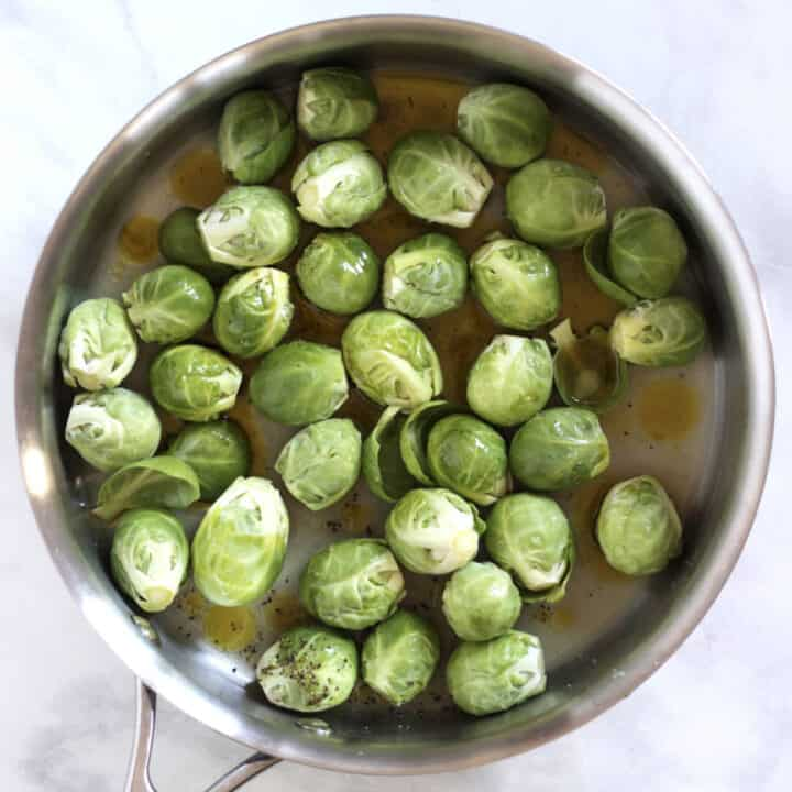 Brussels sprouts scattered over bottom of stainless steel pan with some liquid, salt, and pepper