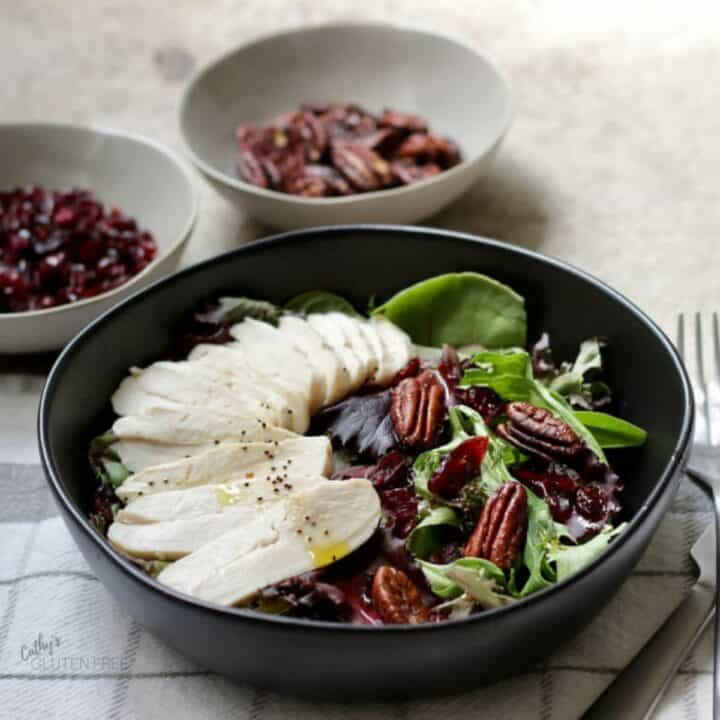 sliced, cooked turkey, dried cranberries, and pecans on a bed of fresh lettuce in black bowl