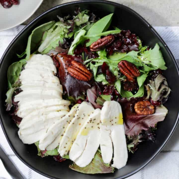sliced chicken on leafy greens with dried cranberries and pecans in black bowl