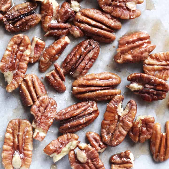 closeup of random pecan halves glistening with maple syrup