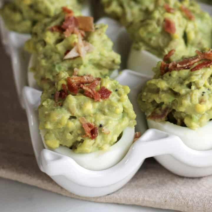 close up of deviled eggs with green filling and bits of bacon on top