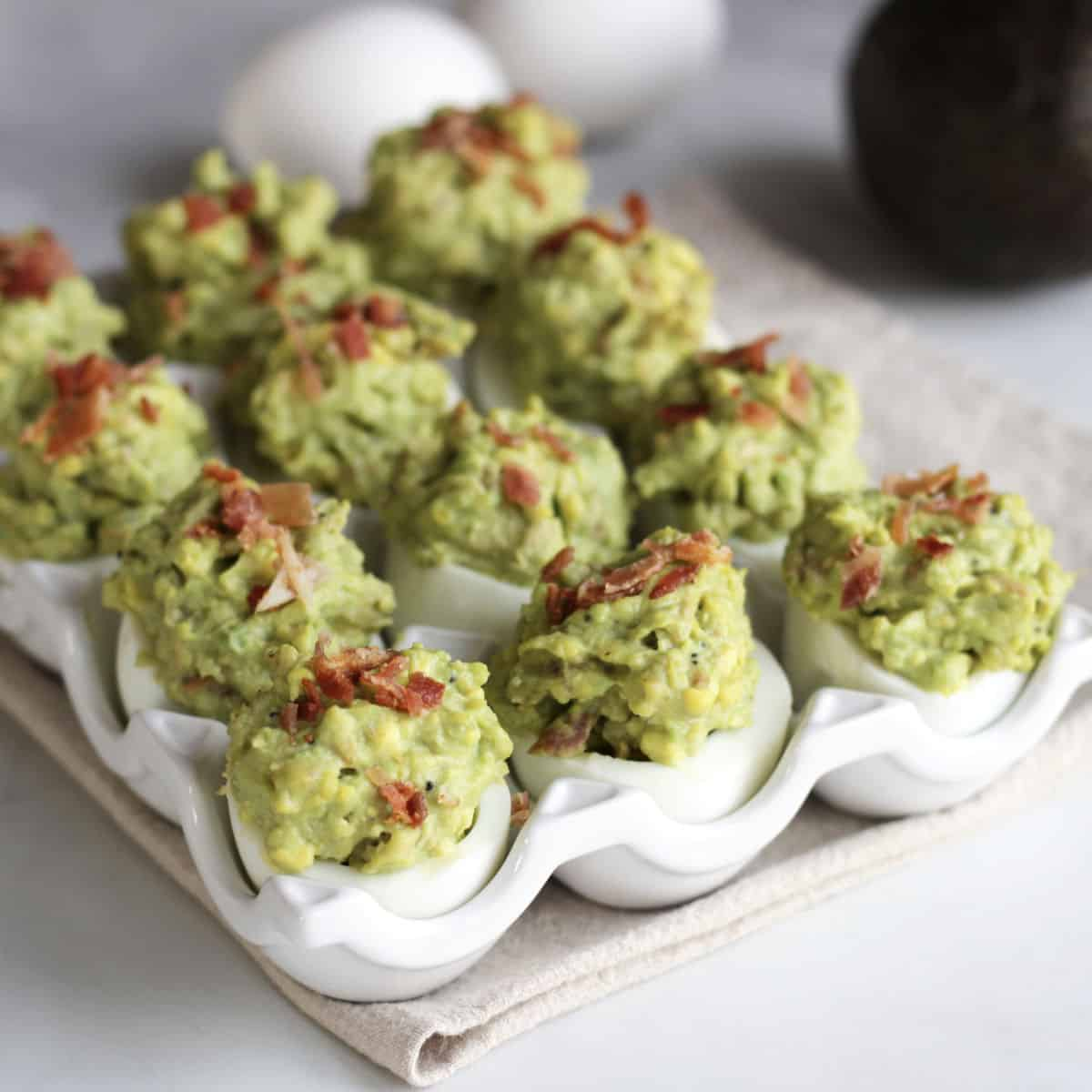 green deviled eggs garnished with chopped bacon in a white dish