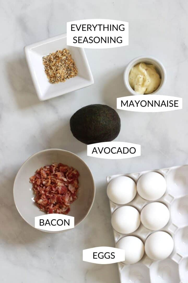 5 ingredients for deviled eggs with bacon laid out individually with labels