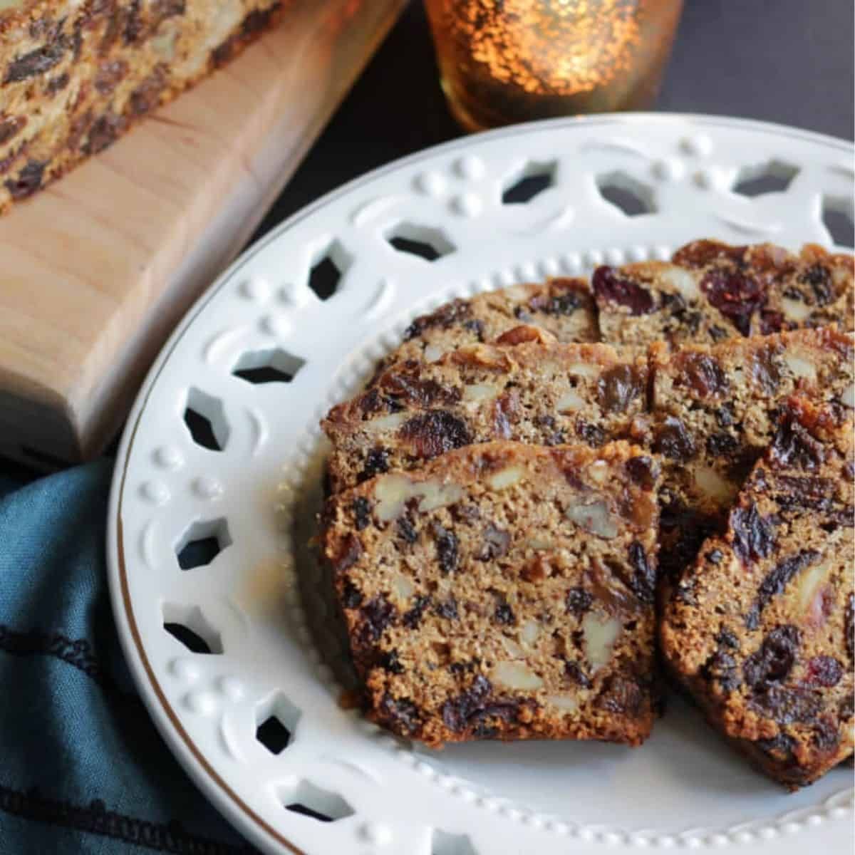 sliced fruitcake with nuts on lacy, white plate