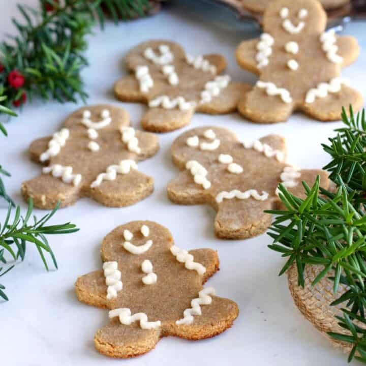 gingerbread men scattered randomly on white marble interspersed with evergreen sprigs