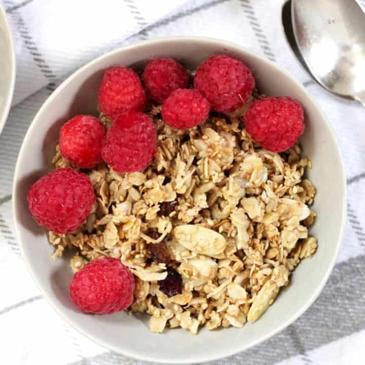 granola with raspberries on top in light grey bowl