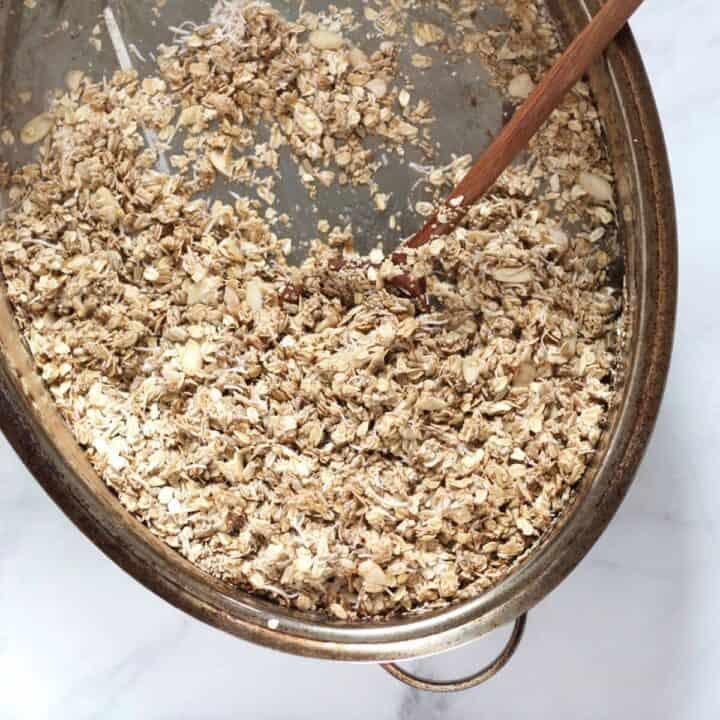 wooden spoon stirring oat mixture in stainless steel roasting pan