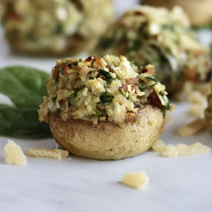 closeup of stuffed mushroom with toasted cheese and spinach topping spilling out