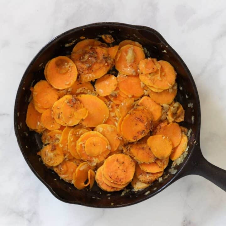 spice mix sprinkled over cooked sweet potato slices in pan