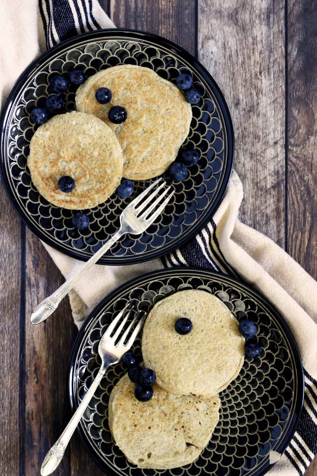 two black plates with two pancakes and some blueberries on each