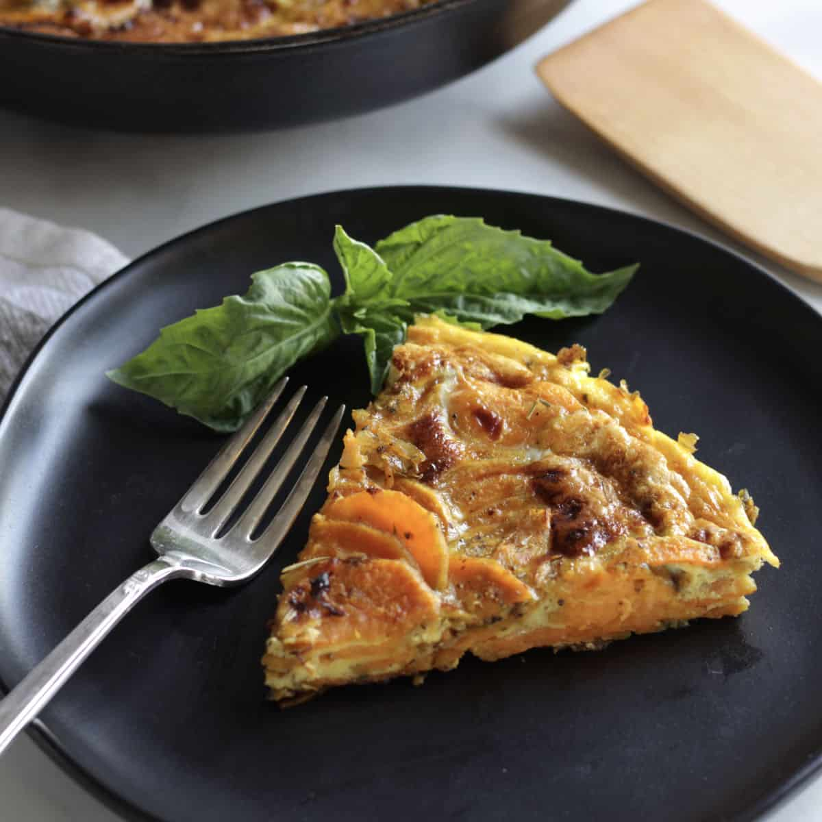 wedge of golden sweet potato frittata with fork and basil garnish on black plate