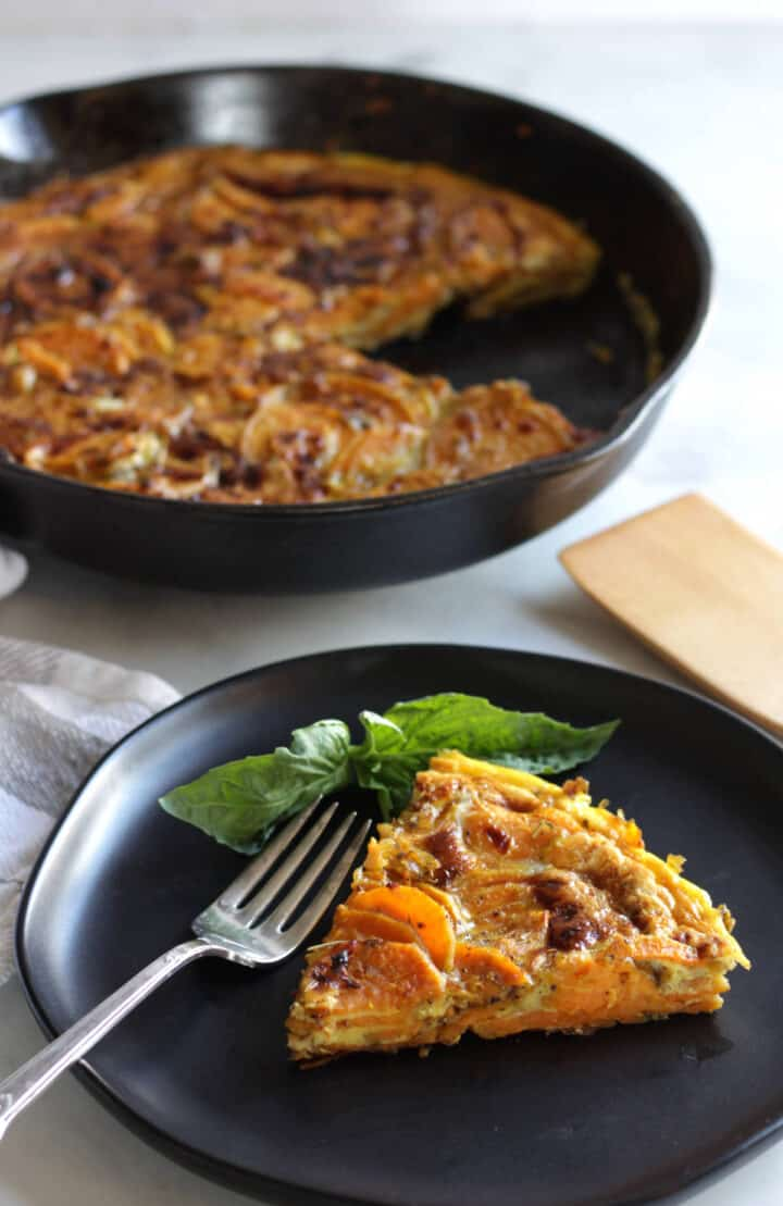 wedge of sweet potato frittata on black plate with remaining frittata in pan in background