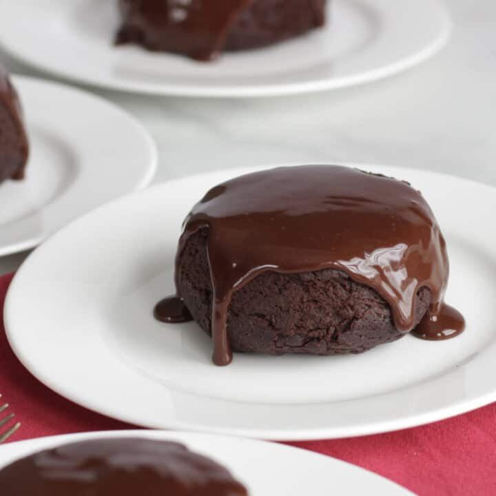 dark brown chocolate ganache dripping over the top and down the sides of a small, round chocolate cake