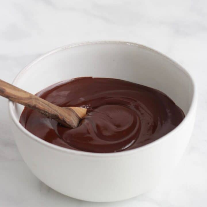 spoon in smooth, liquid dark chocolate in white bowl