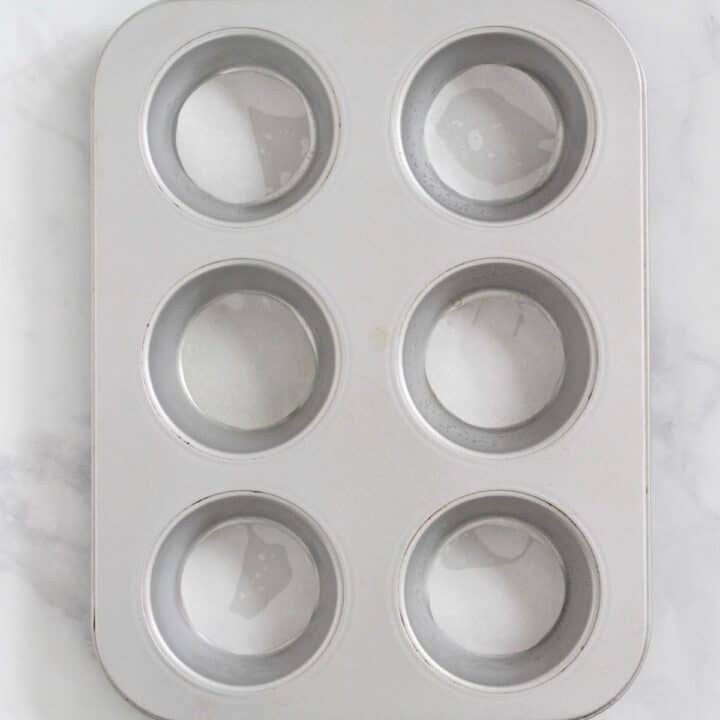 looking into 6-cup muffin pan with round cutouts of parchment paper lining the bottom of each cup