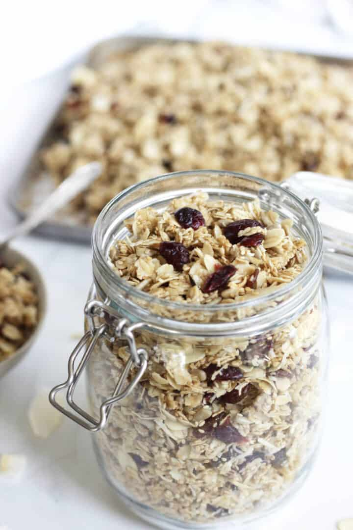 homemade granola in a jar with more granola in a pan in the background