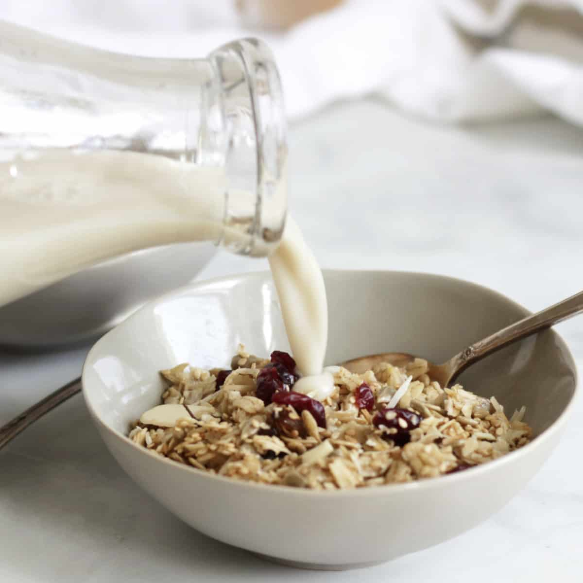 milk pouring from glass bottle onto bowl of granola