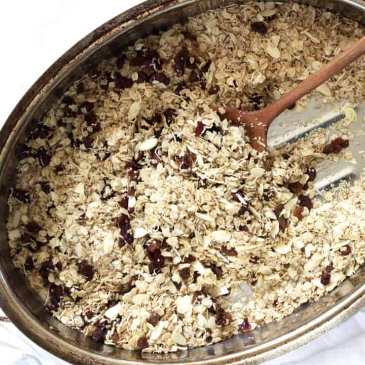 granola with dried raisins and cranberries scattered throughout in a large roasting pan