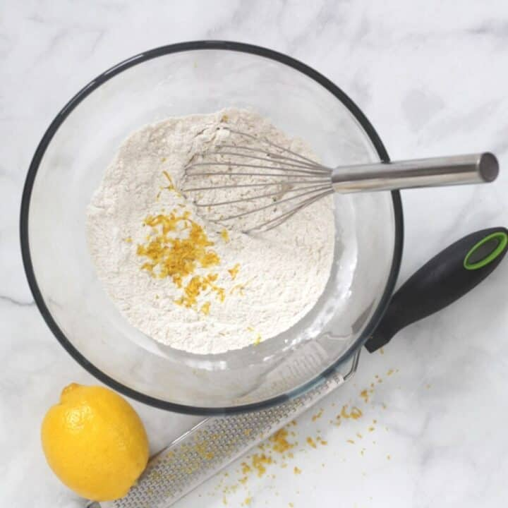 white flour mixture in glass bowl with whisk and grated lemon zest sprinkled on top